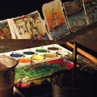 Painting supplies spread out across a table with colorful paintings in the background