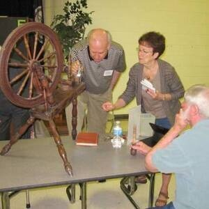 Appraiser reviewing an antique spinning wheel