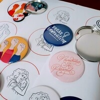 Image is of several buttons and designs for international women's day event including drake innovation logo, fists raised, a revised rosie the riveter