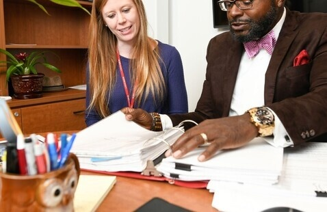 Two employees discuss the contents of a binder.