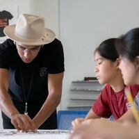 The summer camp instructor demonstrates a technique to watching students