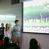 A team of students presents their video game to a crowd