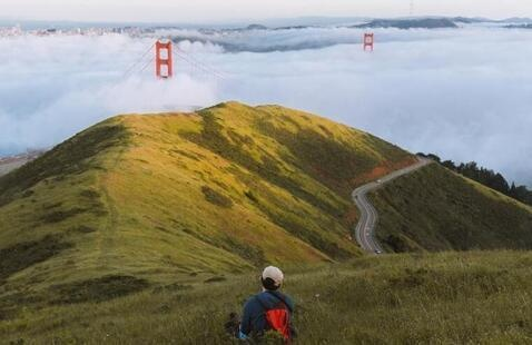 Person sitting on a hill looking at the Golden Gate Bridge and fog