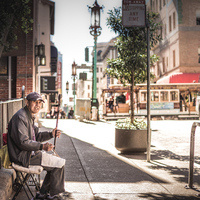 Man playing instrument on street in San Francisco's Chinatown with cable car in the background