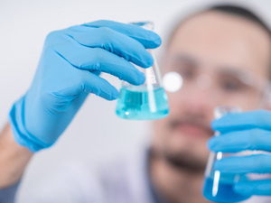 Man holding flasks in lab