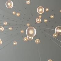 A bunch of lit lightbulbs hanging down on strings from a grey ceiling