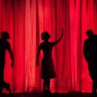 Three silhouettes, two men on each side and one woman in the center, performing on stage against a red curtain