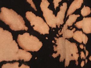 photo of bleach design on black fabric