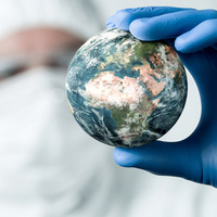 Person wearing protective equipment covering most of body and face, with a gloved hand holding up a globe