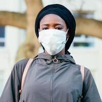 Woman wearing a facial mask standing outside a building
