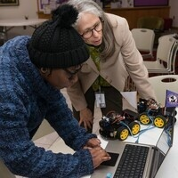 Student and professor with computer and robot