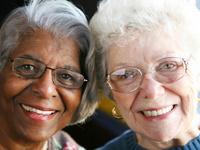 2 female senior citizens smiling together, one Black, one white