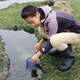 Student at summer camp collects samples from a tidepool.