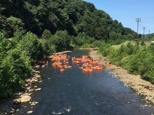 People floating down the Stonycreek river on orange tubes