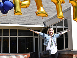 Student standing under balloons spelling out Pitt