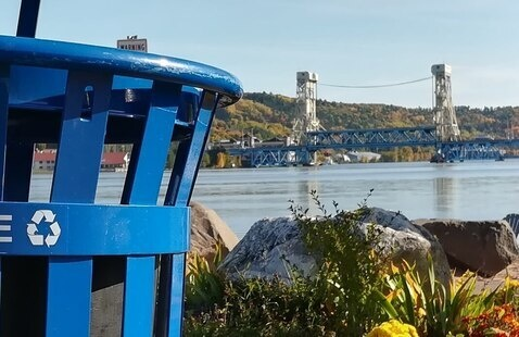 Outdoor recycling bin with Portage Lift Bridge in the background.