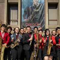 Siskiyou Saxophone Orechestra in front of the SOU Music Building with Jesse Malloy banner