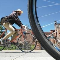 Picture from Daily Camera covering Bike to Work Day. Pictured is a CU Bike Mechanic riding bike