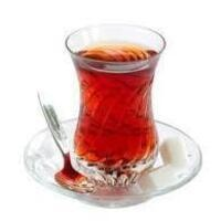 Picture of a glass of tea on a saucer with a spoon.