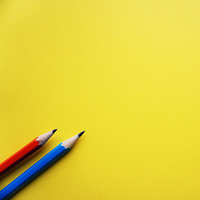 A red pencil and a blue pencil laying next to each other on a yellow background
