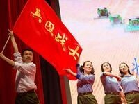 A zhiqing commemorative activity man waves red flag Man and women sing