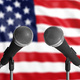 Two mics with an American Flag in the background