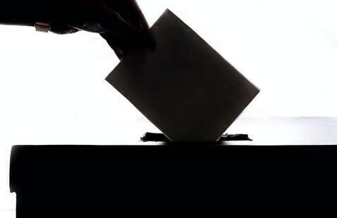 A silhouette of a hand dropping a card into a box