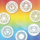 All seven chakras in a circle with a rainbow background