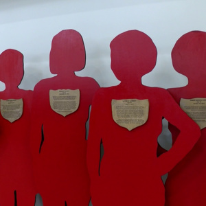 Red silhouettes of four women with plaques highlighting victims of domestic violence stories