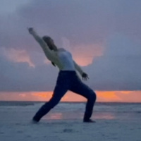 photo of a dancer in front of the ocean at sunset
