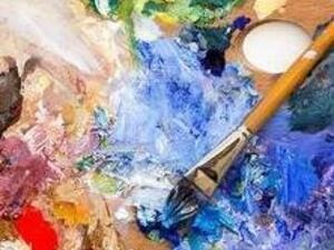 Palette covered in paint with brush
