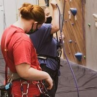 Two women getting ready to go on the climbing wall