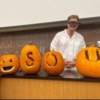 Student in lab coat and goggles / four carved pumpkins spelling SOU