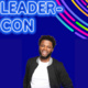 Image Text: Leader-Con. Blue background with a young man standing in front of it smiling.