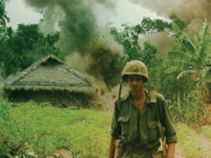 Soldier walking away from smoke and hut in Vietnam