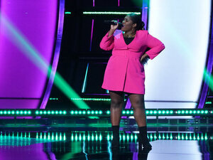Black woman in pink dress singing on the set of NBC's The Voice.