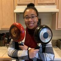 Cassandra holding two skillets in kitchen