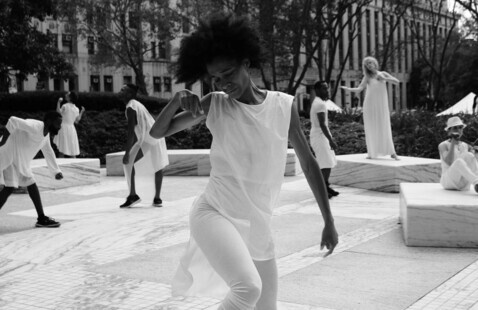 A black and white photo of dancers from Heidi Latsky Dance performing ON DISPLAY at the Federal Plaza in New York City. Each dancer is dressed in all white clothing and in various poses around the plaza. The central figure is a Black woman wearing a white tunic over white leggings. She is in mid movement with her right limbs in a bent position. Her eyes are closed and her face is directed downwards. Photo by Charlotte Jones.