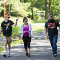 Three students walking along tree-lined path