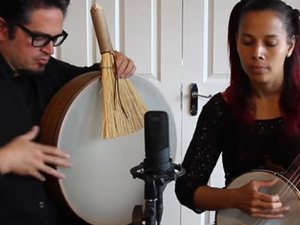 Two musicians performing—man with frame drum and brush and woman with banjo.