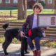 Photo of Professor Acevedo sitting on the bench at Miami's campus on a sunny Fall afternoon. She is a light-skinned Mestiza with short curly brown hair in a plaid jacket, white jeans, blue pants, and maroon boots. She is holding a framed proclamation and presidential medallion to her side. Her service dog Coco, a black standard poodle, stands next to her with his head slightly lowered and placed across her lap. She rests one hand on his shoulder.