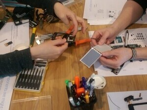 photo of two sets of hands working on Arduino project