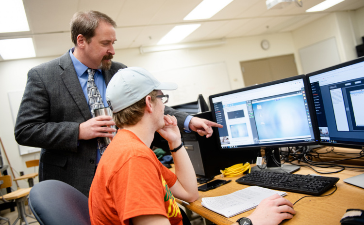 A faculty member shows a student something on a computer monitor.