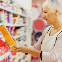 Woman examining label content on box of food