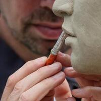 a sculptor's hands working on a sculpture piece