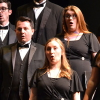individuals in black attire standing and singing