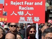 Getty Images: Asian protestors march with signs proclaiming Reject Fear and Racism in English and Chinese