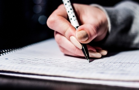 Person with pen in hand, writing on notebook
