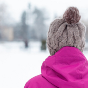 Back of someone's head with stocking cap outside during the winter.
