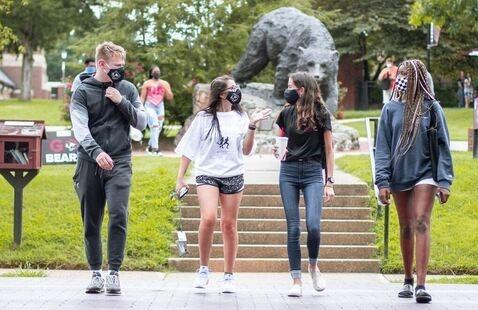 Students talking walking across campus wearing masks